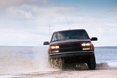 Offroad freedom. Big four-wheel car driving on sandy sea coast in water splashes Stock Photos