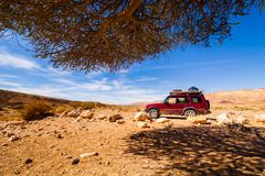 Offroad jeep safari vehicle parked in the middle of the desert Royalty Free Stock Image