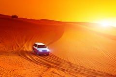 Offroad lastbil- eller suvridningdyn i arabisk öken på solnedgången Offroad har ändrats för att vara oigenkännligt Arkivbild
