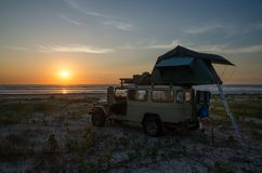 offroad medel 4x4 med taköverkanttältet som campar på stranden under solnedgång, Casamance, Senegal, Afrika Arkivbild