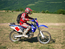 Offroad rider in motion. Offroad rider on motorbike against a summer mountains Stock Images