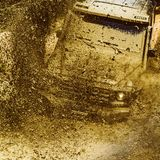 Offroad vehicle coming out of a mud hole hazard. Safari suv. Off-road travel on mountain road. Tracks on a muddy field. Mudding is off-roading through an area stock image
