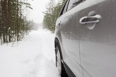 Offroad vehicle on snowy forest road, side view Royalty Free Stock Photos