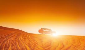 Offroad vrachtwagen of suv berijdend duin in Arabische woestijn bij zonsondergang Offroad is gewijzigd niet erkend om te zijn Stock Foto
