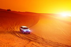 Offroad vrachtwagen of suv berijdend duin in Arabische woestijn bij zonsondergang Offroad is gewijzigd niet erkend om te zijn Stock Fotografie