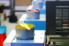 Offset ink cans. Offset printing machine with color ink cans with spatulas, landscape oriented photo, focused to yellow color ink can Royalty Free Stock Photo