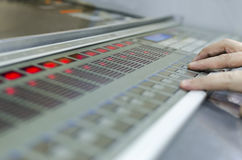 Offset machine press print run at table. Hands on fountain key control unit close-up stock photo