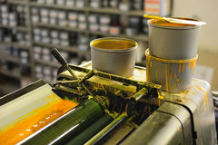 Offset printing machine. Detail of the offset printing machine with cans of yellow color stock images