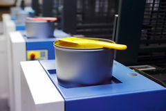 Offset printing machine - color ink cans. Focused to can with yellow color royalty free stock images