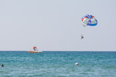 Offshore boat rolls of people on a parachute on the Black Sea coast Royalty Free Stock Photos