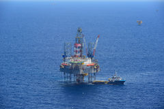 The offshore drilling oil rig and supply boat side view Stock Photos