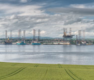 Offshore drilling platform in repair in shipyards in Dundee. Offshore drilling platform in repair in shipyard in Dundee looking accross a green field and accross Stock Photos