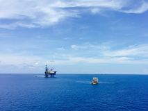 Panorama of offshore drilling rig with supply boat. Offshore drilling rig in the ocean with supply boat transport the equipment Royalty Free Stock Photography