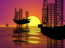 OFFSHORE DRILLING RIG-OIL WELL AT SUNSET. Three Silhouette Offshore Oil drilling Rigs Against a Sunset Background Stock Photo