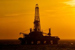 Offshore drilling rig during sunset stock photography