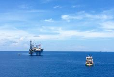 Offshore drilling rig with supply boat. Offshore drilling rig in the ocean with supply boat transport the equipment Royalty Free Stock Photography