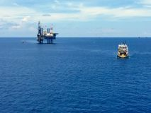 Offshore drilling rig with supply boat. Offshore drilling rig in the ocean with supply boat transport the equipment Stock Photo