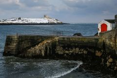 Dalkey island. Dublin. Ireland. Offshore island covered with snow with the ruins of an old church and a martello tower viewed from Colliemore harbour. Dalkey Royalty Free Stock Photo