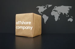 Offshore. Companies around the world. On the Box an  company is written. In the background a world map Royalty Free Stock Images