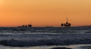 Offshore oil drilling rigs at sunset. Offshore oil drilling platforms and an oil tanker ship in the ocean at sunset in Southern California royalty free stock image