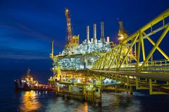 Offshore oil and gas central processing platform while offloading cargo to vessel. Royalty Free Stock Image
