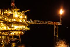 Offshore oil and Gas central processing platform and remote plat. Form produced natural gas and liquid condensate for set to onshore refinery in night scene stock image