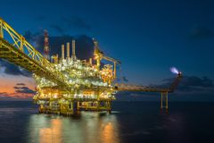Offshore oil and gas central processing platform in sun set where produced raw gases and treat then sent to onshore refinery. Offshore oil and gas central royalty free stock images