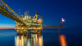 Offshore oil and gas central processing platform in sun set which produce raw gas, crude and hydrocarbon then sent to onshore. Refine, petrochemical industry stock photo