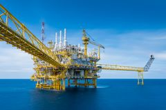 Offshore oil and gas construction platform in operation produce raw product for sent to onshore refinery and petroleum industry. stock photo