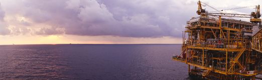 Offshore oil and gas rig platform with beautiful sunset time wit. H storm of clouds in the gulf of Thailand for business industrial concept panorama view Stock Image