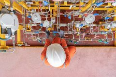 Offshore oil and gas service worker operating diaphragm pump by adjusting stroke of pump. royalty free stock photography