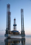 Offshore oil rig. With reflection in calm waters Stock Image