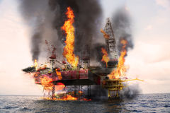 Offshore oil and rig construction damaged because worst case or fire case which can`t control situation. Oil spill into the sea Royalty Free Stock Photo