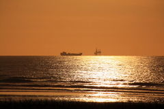 Offshore oil rig and ocean ship. Calm ocean at sunset at the dutch coast with offshore oil rig and ship in the background Royalty Free Stock Image