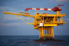 Offshore oil and rig platform in sunset or sunrise time. Construction of production process in the sea. Power energy of the world Stock Images