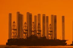 Offshore oil rig at shallow wa. Ters during sunset Royalty Free Stock Photos