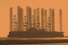 Offshore oil rig at shallow wa. Offshore oil rig at shallow  waters during sunset Royalty Free Stock Photo