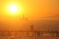 Offshore oil rig at sunset. An offshore oil rig lit from behind by the setting sun which is going down in a blaze of glory royalty free stock image