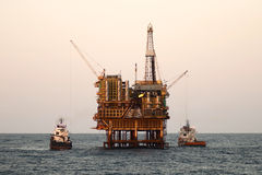 Offshore  oil rig with supply boats. Stock Images