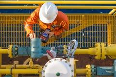 Offshore oil rig worker calibrating coriolis digital flow meter at processing platform.