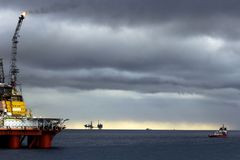 Offshore platforms, standby vessel, sea & clouds royalty free stock photos
