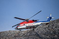 Tricolor  rescue helicopter in red, white and blue comes down for landing. royalty free stock photos