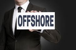 Offshore sign is held by businessman Stock Image