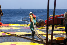 Offshore vessel crew working on deck. Ship crew working on deck during hose lifting operation at sea stock image
