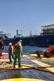 Offshore vessel crew working on deck. Ship crew working on deck during hose lifting operation at sea stock images