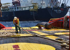 Offshore vessel crew working on deck. Ship crew working on deck during hose lifting operation at sea royalty free stock photo