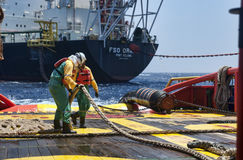 Offshore vessel crew working on deck. Ship crew working on deck during hose lifting operation at sea royalty free stock photography