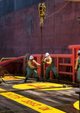 Offshore vessel crew working on deck. Ship crew working on deck during hose lifting operation at sea stock photos