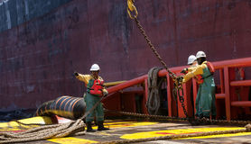 Offshore vessel crew working on deck. Ship crew working on deck during hose lifting operation at sea stock photo