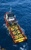Offshore vessel at sea. Supply boat view from top during cargo lifting operation at platform royalty free stock images